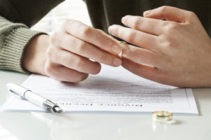Person's Hand Taking off Wedding Ring After Signing Divorce Form